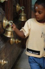 Boy with a bell at a Hindu temple